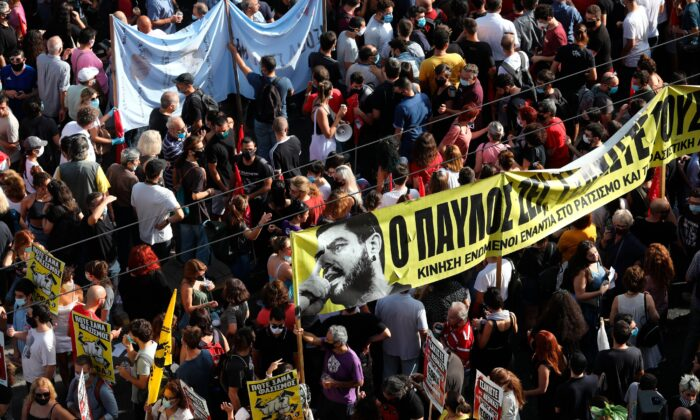 People holding a banner depicting Greek rap singer Pavlos Fyssas, who was stabbed and killed by a supporter of the Golden Dawn party in 2013, gather for a protest outside a court in Athens, on Oct. 7, 2020. (Yorgos Karahalis/AP Photo)