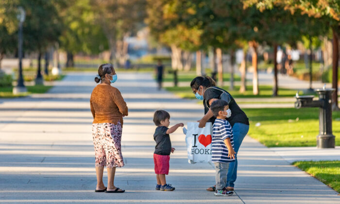 A family walks away from a book drive at the public library in Westminster, Calif., on Sept. 22, 2020. (John Fredricks/The Epoch Times)