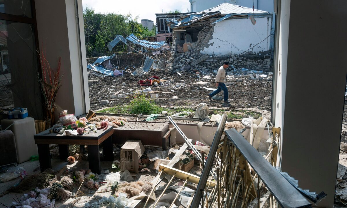 A man walks past a house destroyed by shelling