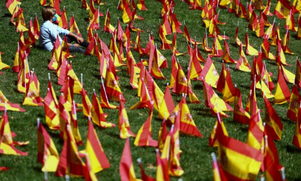 A person sits next to Spanish flags