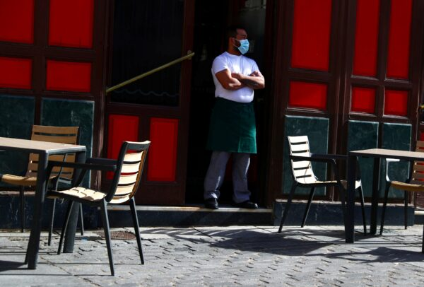 A waiter wearing a protective face mask waits for customers