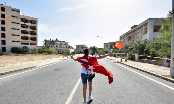 A woman walks while holding Turkish and Turkish Cypriot flags