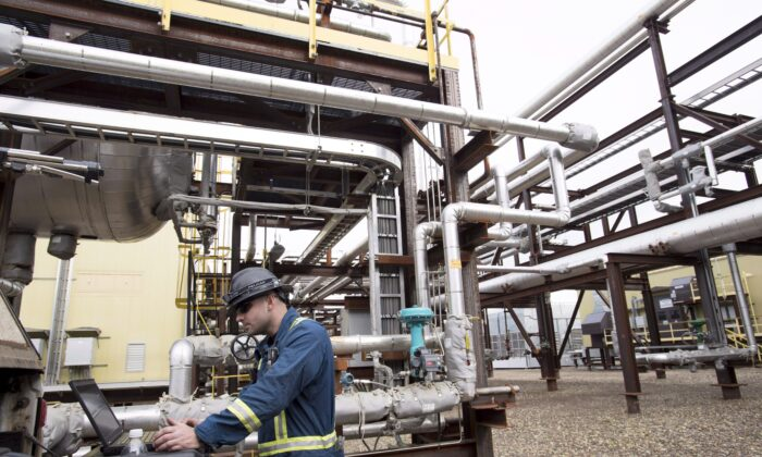 An instrumentation craftsman is seen working outside the Shell Saturn natural gas plant outside of Fort St. John, B.C., Thursday, Oct. 11, 2018. THE CANADIAN PRESS/Jonathan Hayward