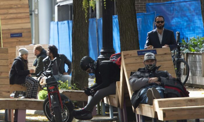 People relax on Saint Catherine Street in Montreal on the first day of a 28-day lockdown of bars and restaurants in the city, on October 1, 2020. (The Canadian Press/Ryan Remiorz)