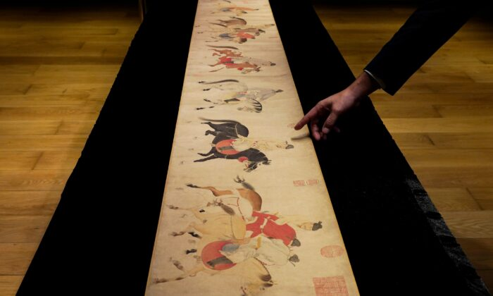 """A Sotheby's employee presents the Chinese scroll, """"Five Drunken Princes Returning on Horseback"""" from the period of Chinese Yuan Dynasty, by Ren Renfa during a media preview for the Sotheby's in Hong Kong, China, on Sept. 23, 2020. (Vincent Yu/AP Photo)"""
