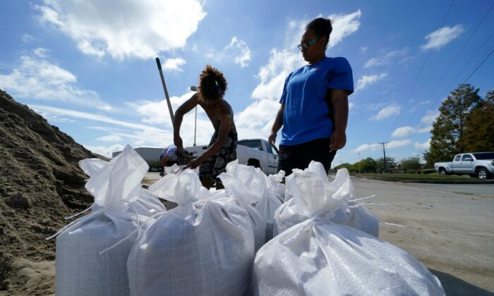 Stephanie Verrett and Jodie Jones fill sandbags to protect their home in anticipation of Hurricane Delta, in Houma, La., on Oct. 7, 2020. (Gerald Herbert/AP Photo)