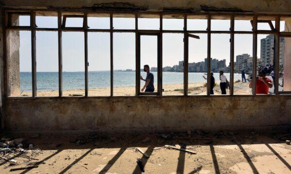 People awalk on a abandoned beach in Varosha