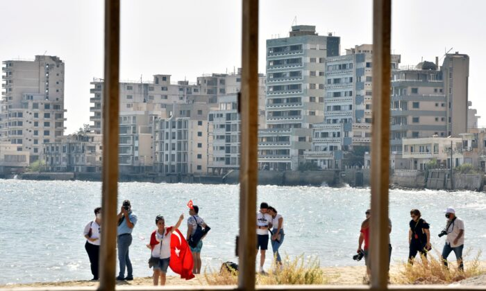People walk on a beach inside an area fenced off by the Turkish military since 1974 in the abandoned coastal area of Varosha, a suburb of the town of Famagusta in Turkish-controlled northern Cyprus, on Oct. 8, 2020. (Harun Ucar/Reuters)