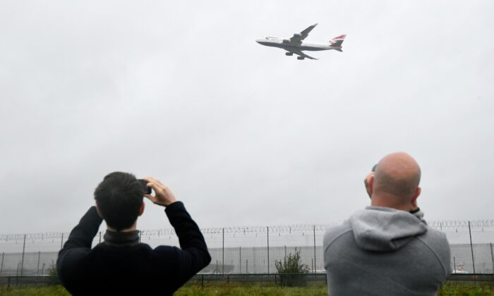 Spectators take images of a British Airways Boeing 747 as it does a flypast over London Heathrow airport on it's final flight, the last of 31 jumbo jets to be retired early by the airline due to the coronavirus disease (COVID-19) pandemic, in London, Britain, on Oct. 8, 2020. (Toby Melville/Reuters)