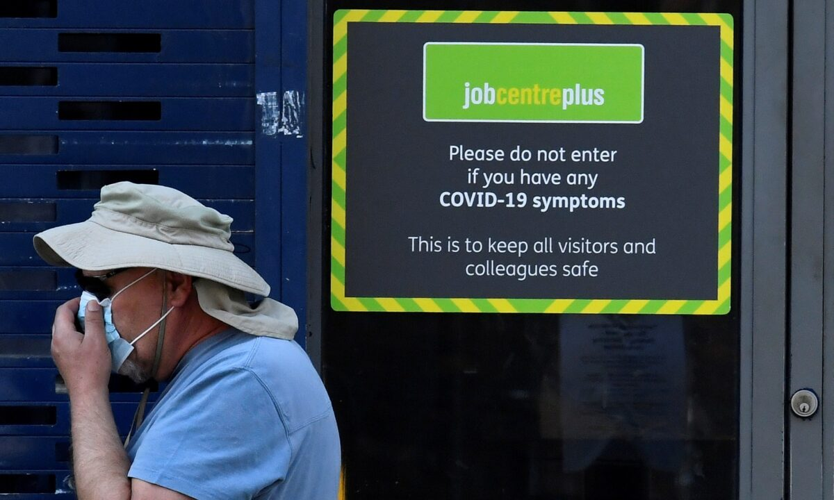 A person wearing a protective face mask walks past a Job Centre Plus office