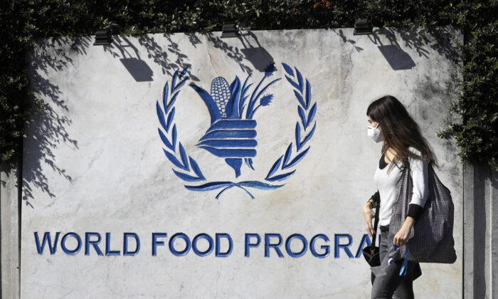 A woman walks past a sign at the entrance of the United Nations World Food Program (WFP), in Rome on Oct. 9, 2020. (AP Photo/Gregorio Borgia)