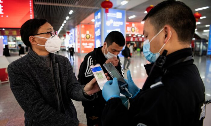 A passenger shows a green QR code on his phone to show his health status to security upon arrival at the Wenzhou railway station in Wenzhou, China on Feb. 28, 2020. (Noel Celis/AFP via Getty Images)