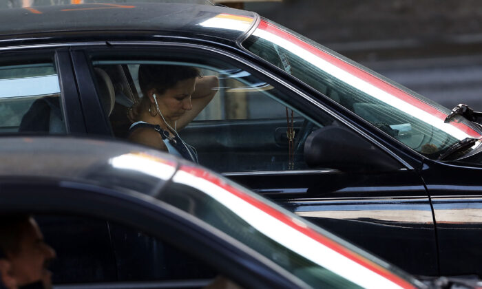 A driver uses a phone with earphones on while behind the wheel of a car in New York City in a file photo. (Spencer Platt/Getty Images)