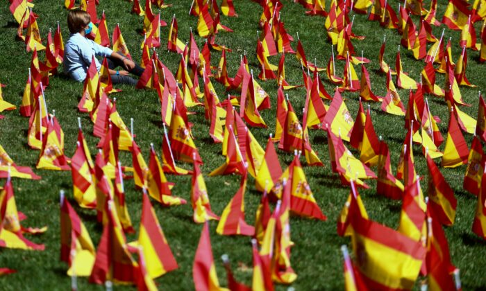 A person sits next to Spanish flags set up in memory of the CCP virus disease (COVID-19) victims in a park, in Madrid, Spain, on Sept. 27, 2020. (Sergio Perez/Reuters)