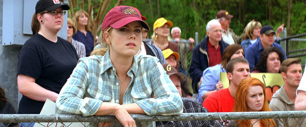 "woman with red baseball cap leans on fence in ""Trouble with the Curve"""