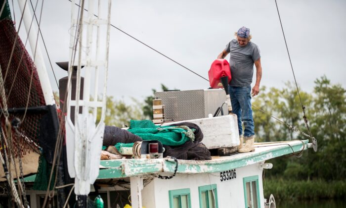 Timothy Schouest adds diesel to his boat's generator in preparation for Hurricane Delta at Bayou Carlin Cove, in Delcambre, La., on Oct. 8, 2020. (Leslie Westbrook/The Advocate via AP)