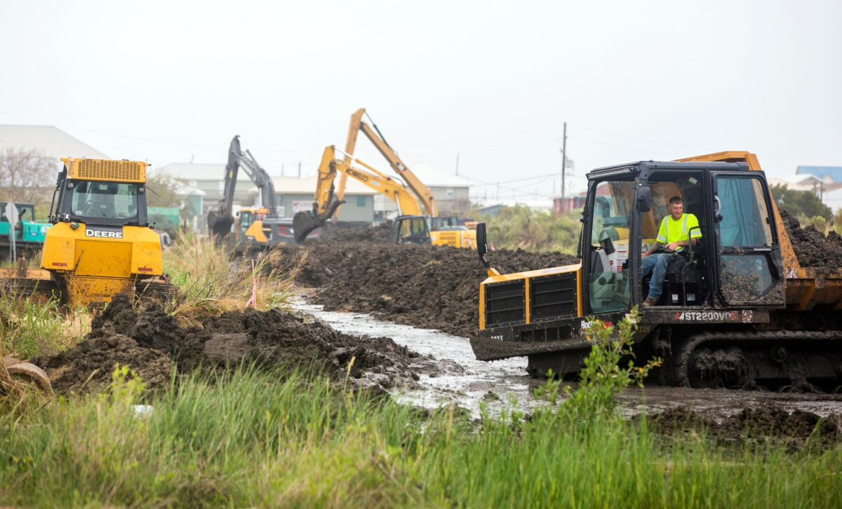 Workers extend a tidal levee 1,300 feet