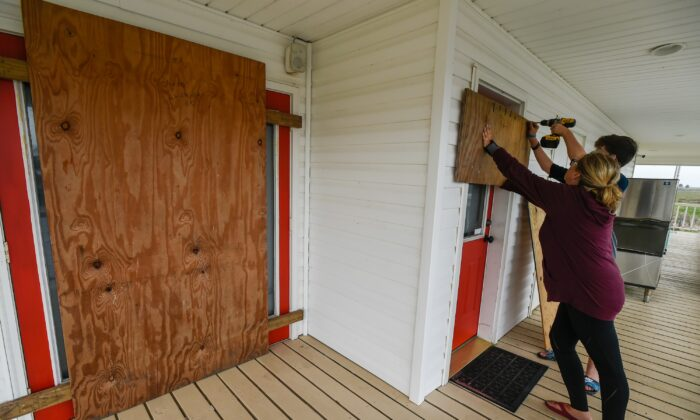 Residents Mamie Russo and her son Cole attach wood to their front door while preparing for Hurricane Delta in Cypremort Point, La., on Oct. 8, 2020, (Brad Kemp/The Advocate via AP)