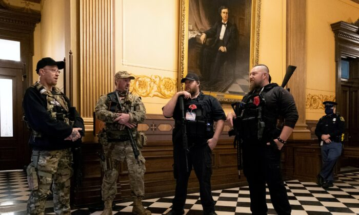 Members of a militia group, including Michael John Null and Willam Grant Null, right, who were charged on Oct. 8, 2020, for their involvement in a plot to kidnap the Michigan governor, attack the state Capitol Building, and incite violence, stand near the doors to the chamber in the capitol building before the vote on the extension of Gov. Gretchen Whitmer's emergency declaration/stay-at-home order in Lansing, Mich., April 30, 2020. (Seth Herald/Reuters)