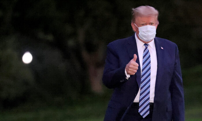 President Donald Trump gestures upon return to the White House from Walter Reed National Military Medical Center in Washington on Oct. 5, 2020. (Win McNamee/Getty Images)