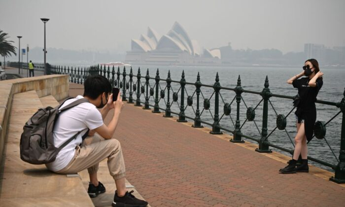 Tourists wearing masks take photos as the Opera House (back, C) is enveloped in haze caused by nearby bushfires, in Sydney on December 10, 2019. (PETER PARKS/Getty Images)