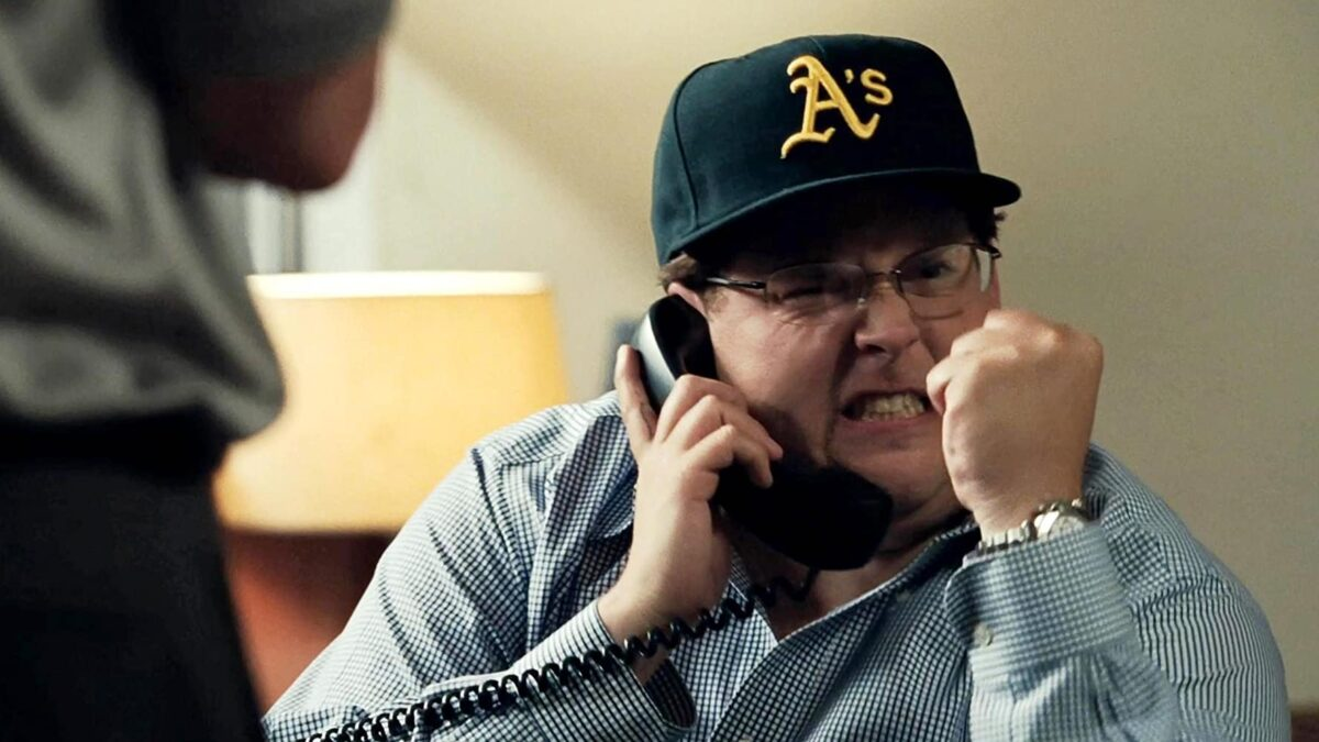 """man in oakland A's hat on phone in """"Moneyball"""""""