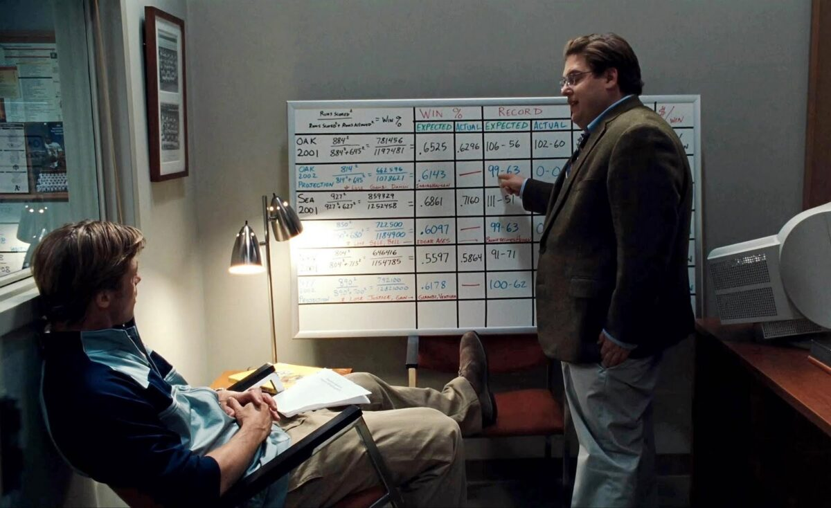 """man seated and man at whiteboard in """"Moneyball"""""""