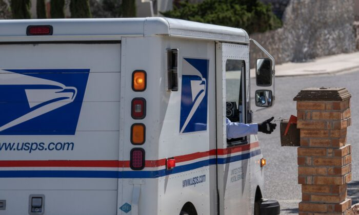 A United States Postal Service mail carrier delivers mail in El Paso, Texas, on April 30, 2020. (Paul Ratje/AFP via Getty Images)