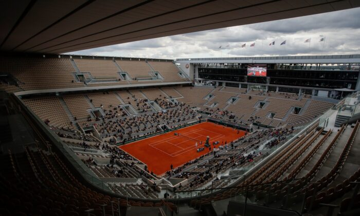 Rows of empty seats are seen at center court Philippe Chatrier as Serbia's Novak Djokovic and Spain's Rafael Nadal warm up for the final match of the French Open tennis tournament at the Roland Garros stadium in Paris, France, on Oct. 11, 2020. (Alessandra Tarantino/AP Photo)