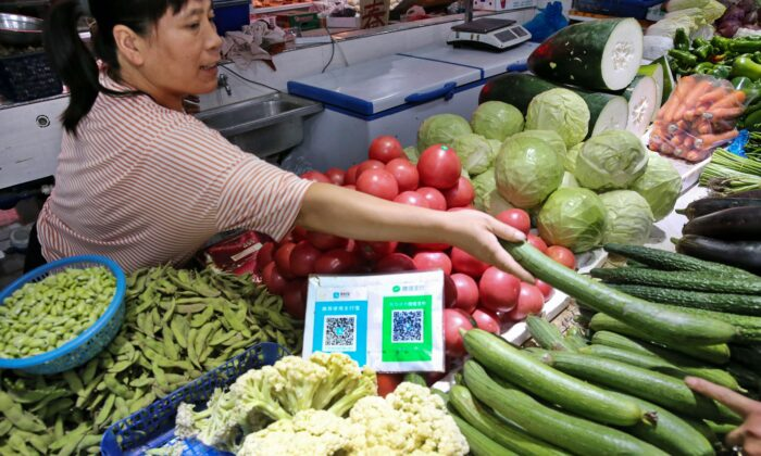 Alipay and WeChat QR codes for online payment are displayed as a vendor (L) gives vegetables to a customer at a market in Nantong, Jiangsu Province, China, on Sept. 10, 2018.  (STR/AFP via Getty Images)