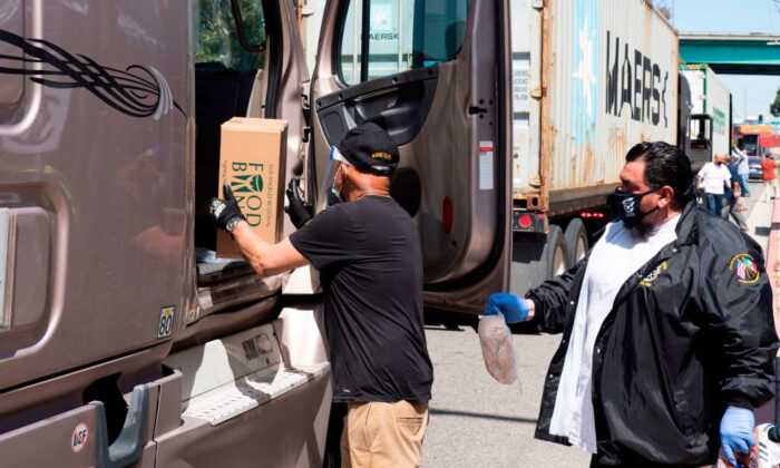 Teamsters Union members and the Los Angeles Regional Food Bank distribute food to hundreds of port truck drivers impacted by the COVID-19 pandemic during a mobile drive-through food pantry in Long Beach, Calif., on April 22, 2020. (Robyn Beck/AFP via Getty Images)