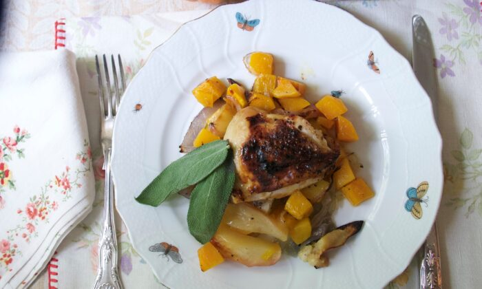 As the chicken thighs roast, they release their juices and fat to mingle with the caramelizing squash and apples on the same pan. (Victoria de la Maza)