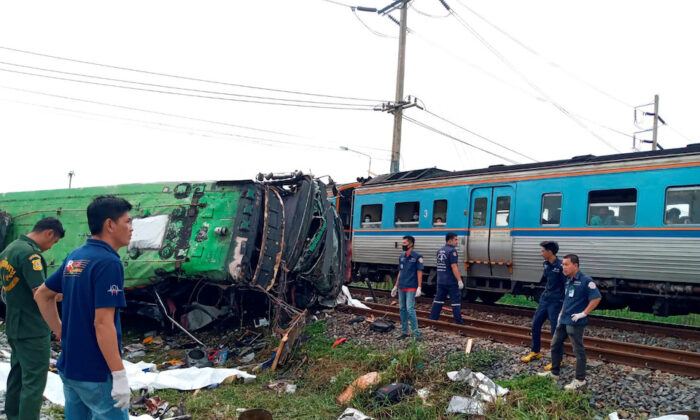 Rescue workers stand at the crash site where a train collided with a paseengers bus in Chacheongsao province in central Thailand on Oct.11, 2020.(Dailynews via Reuters)