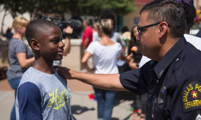 A police officer talks with a boy at a memorial at Dallas Police Headquarters on July 8, 2016. (Laura Buckman/AFP via Getty Images)