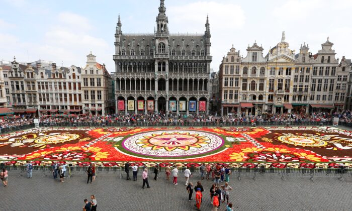The installation of the annual flower carpet on the Grand Place in the city center of Brussels on Aug. 16, 2018. (NICOLAS MAETERLINCK/AFP via Getty Images)