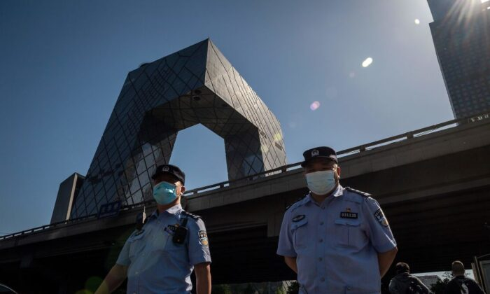 Police officers wearing masks walk as the China Central Television (CCTV) headquarters building (L, back) is seen in Beijing on May 19, 2020. (Nicolas Asfouri/AFP via Getty Images)
