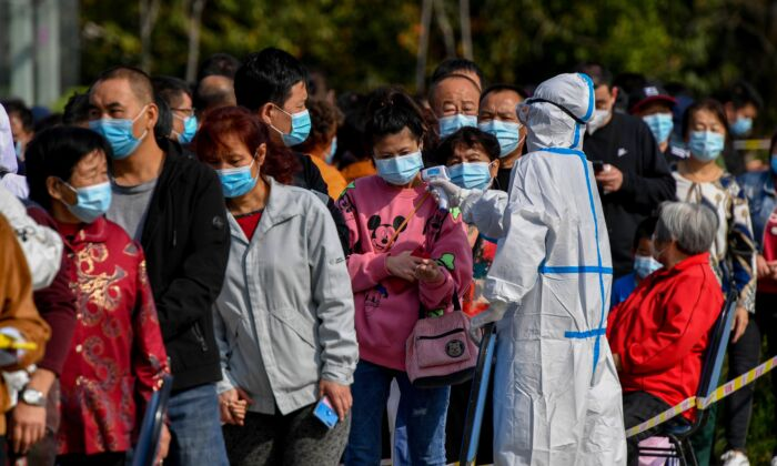 A health worker checks the temperature of residents as they line up to be tested for the COVID-19 in Qingdao, eastern China's Shandong Province on Oct. 12, 2020. (STR/AFP via Getty Images)