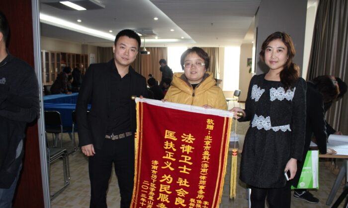 Homeowners express gratitude to Zhang Shichao (left) for protecting their property rights through legal means, in Jinan, in November 2013. (Courtesy of Zhang Shichao)