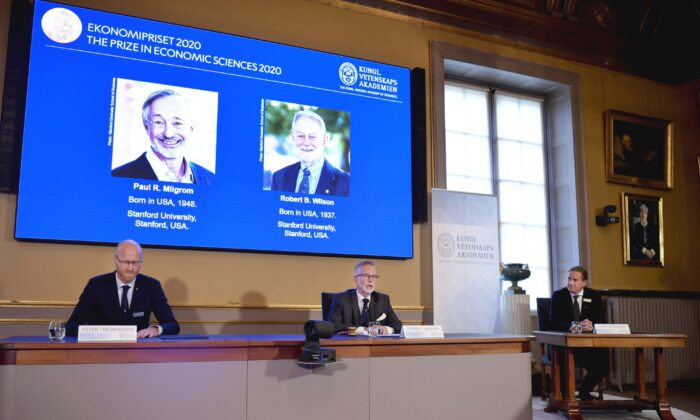 Peter Fredriksson, Chairman of the Committee for Economic Sciences, left, Goran K. Hansson, Permanent Secretary for the Royal Swedish Academy of Sciences, center, and Tommy Andersson, member in The Prize Committee for the Alfred Nobel Memorial Prize in Economic Sciences announce the Sveriges Riksbank Prize in Economic Sciences in Memory of Alfred Nobel for 2020 at a press conference in Stockholm on Oct. 12, 2020. (Anders Wiklund/TT via AP)