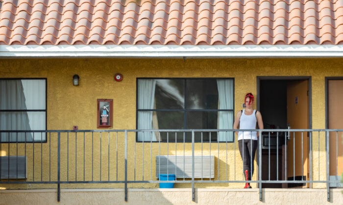 A Project Roomkey participant stands outside her door at the Stanton Inn in Stanton, Calif., on Oct. 8, 2020. (John Fredricks/The Epoch Times)