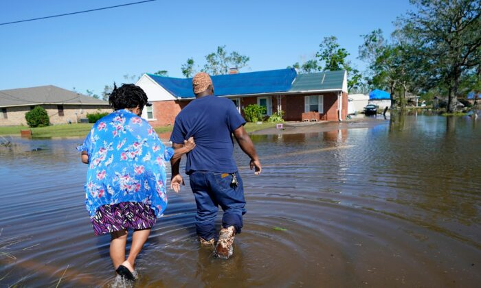 Soncia King holds onto her husband Patrick King as they walk through the flooded street to their home, after Hurricane Delta moved through on Friday, in Lake Charles, La., on Oct. 10, 2020. (Gerald Herbert/AP Photo)