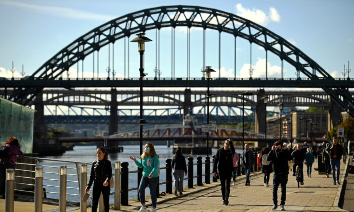 People, some wearing a face mask or covering due to the COVID-19 pandemic, walk along the bank of the River Tyne, near the Tyne Bridge, in Newcastle, northeast England on Sept. 29, 2020, after tighter restrictions were put in place to help mitigate the spread of COVID-19. (Oli Scarff/AFP via Getty Images)