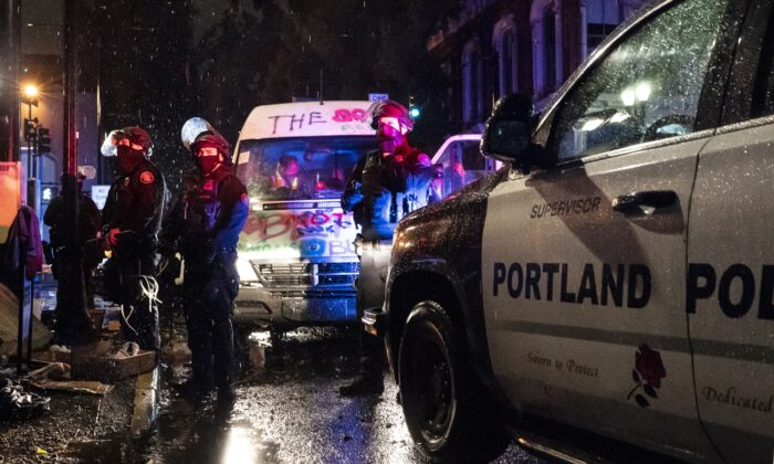 Police detain passengers of a van linked to rioting, in Portland, Ore., on Oct. 11, 2020. (Nathan Howard/Getty Images)