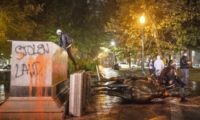 People stand near the toppled statue of President Theodore Roosevelt during a riot in Portland, Ore., Oct. 11, 2020. (Nathan Howard/Getty Images)