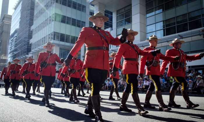 Members of the RCMP march during the Calgary Stampede parade in Calgary on July 6, 2018. (The Canadian Press/Jeff McIntosh)