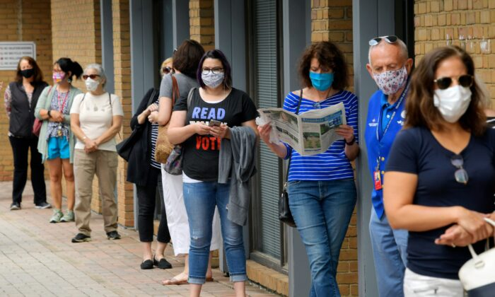 Alexandria residents wait in a socially distanced line to cast their ballots for the November presidential election on first day of early voting in Virginia, at the Voter Registration Office in Alexandria, Va., on Sept. 18, 2020. (John McDonnell/The Washington Post via AP)