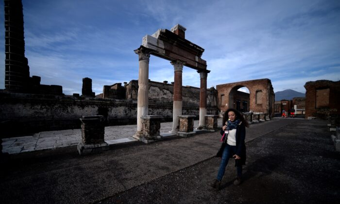 A visitor walks across the Roman Forum on November 25, 2019 in Pompeii. - While treasure hunters regularly pillaged Pompeii down the centuries looking for precious jewels or artifacts, whole areas have yet to be explored by modern-day archaeologists. (Photo by FILIPPO MONTEFORTE/AFP via Getty Images)