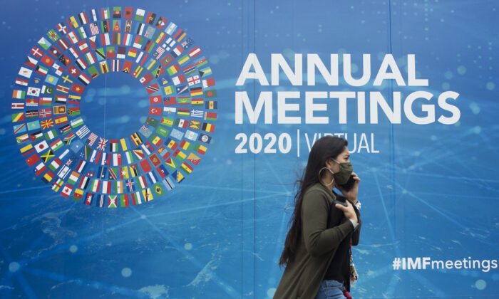 A woman walks past a promotional poster for the virtual 2020 Annual Meetings outside the International Monetary Fund at their headquarters in Washington, on October 13, 2020. (ANDREW CABALLERO-REYNOLDS/AFP via Getty Images)