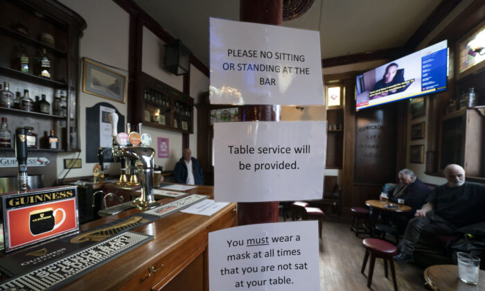 People sit in the Dispensary pub in Liverpool, England, on Monday, Oct. 12, 2020. The British government has carved England into three tiers of risk in a bid to slow the spread of a resurgent CCP virus. The northern city of Liverpool is in the highest category and will close pubs, gyms, and betting shops. (Jon Super/AP Photo)