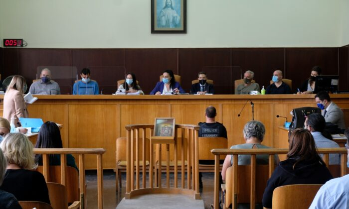 """Yiannis Paraskakis, bottom right, who accused of the brutal killing of American biologist Suzanne Eaton in 2019, wearing a bulletproof vest that reads """"Greek Police,"""" sits in the court room on the first day of the trial in Rethymno, on the Greek island of Crete, on Oct. 13, 2020. (Giannis Angelakis/AP Photo)"""